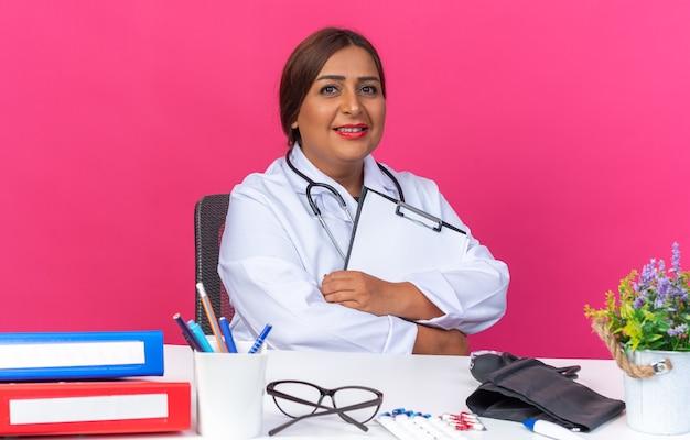 Medico della donna di mezza età in camice bianco con lo stetoscopio che tiene appunti guardando sorridente fiducioso seduto al tavolo con cartelle per ufficio su sfondo rosa