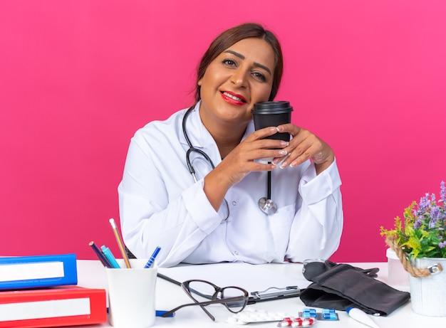 Medico della donna di mezza età in camice bianco con lo stetoscopio che tiene la tazza di caffè che sorride allegramente seduto al tavolo con le cartelle dell'ufficio sul muro rosa