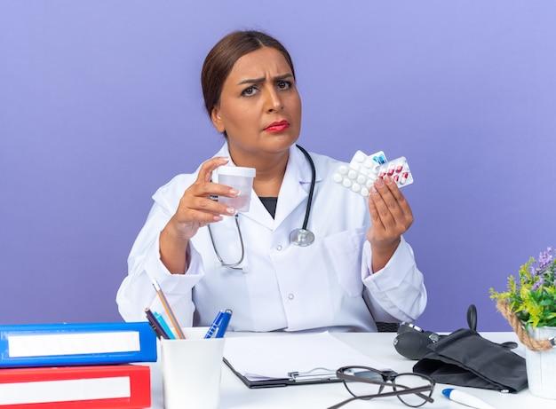 Medico donna di mezza età in camice bianco con stetoscopio che tiene diverse pillole e vaso di prova con faccia seria seduta al tavolo su blue