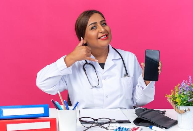 Medico della donna di mezza età in camice bianco con lo stetoscopio che tiene lo smartphone che fa il gesto di chiamarmi sorridendo allegramente seduto al tavolo con le cartelle dell'ufficio sul rosa
