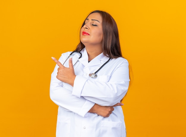 Medico della donna di mezza età in camice bianco con lo stetoscopio che osserva da parte con l'espressione fiduciosa seria che indica con il dito indice al lato che sta sopra la parete arancione