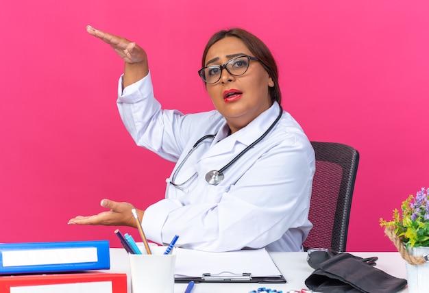 Medico della donna di mezza età in camice bianco con lo stetoscopio che osserva che mostra il gesto di dimensione con le mani che si siedono al tavolo con le cartelle dell'ufficio sopra fondo rosa
