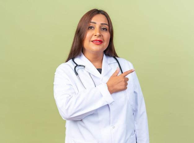 Medico della donna di mezza età in camice bianco con lo stetoscopio che sorride fiducioso che indica con il dito indice al lato che sta sopra la parete verde