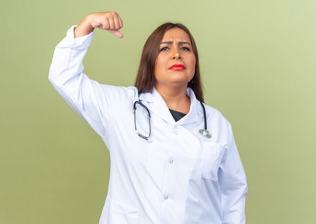 Medico della donna di mezza età in camice bianco con lo stetoscopio con l'espressione fiduciosa seria che alza il pugno che sta sul green
