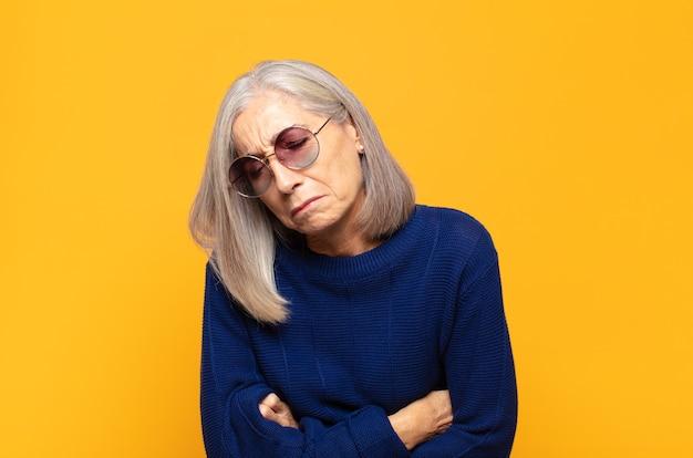 Donna di mezza età che si sente ansiosa, malata, malata e infelice, che soffre di dolori allo stomaco o influenza