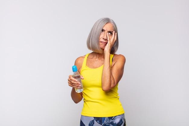 Donna di mezza età che si sente annoiata, frustrata e assonnata dopo un compito noioso, noioso e noioso, tenendo il viso con la mano. concetto di fitness