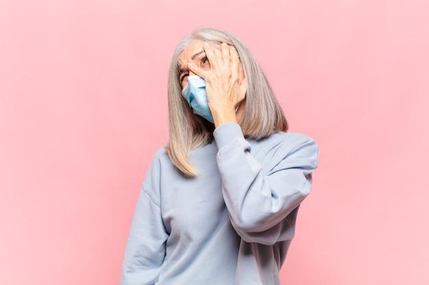 Donna di mezza età che si sente annoiata, frustrata e assonnata dopo un compito noioso, noioso e noioso, tenendo la faccia con la mano