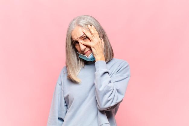 Donna di mezza età che si sente annoiata, frustrata e assonnata dopo un compito noioso e noioso, tenendo la faccia con la mano