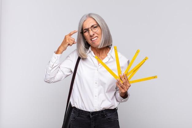 Donna di mezza età che si sente confusa e perplessa, mostrando che sei pazzo, pazzo o fuori di testa