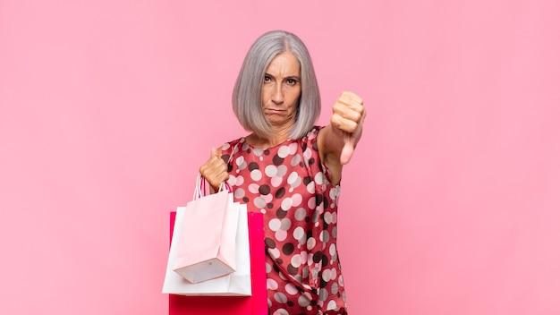 Donna di mezza età che si sente arrabbiata, arrabbiata, infastidita, delusa o scontenta, mostrando il pollice verso con uno sguardo serio con le borse della spesa