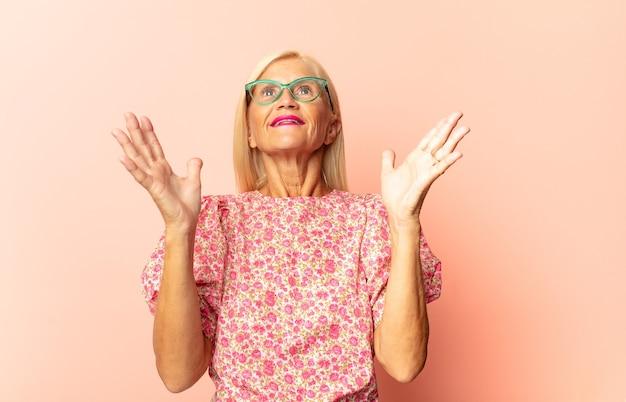 Donna di mezza età che si sente felice, stupita, fortunata e sorpresa, come dire sul serio omg? incredibile