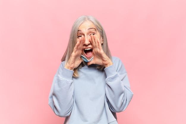 Donna di mezza età che si sente felice, eccitata e positiva, dando un grande grido con le mani vicino alla bocca, chiamando