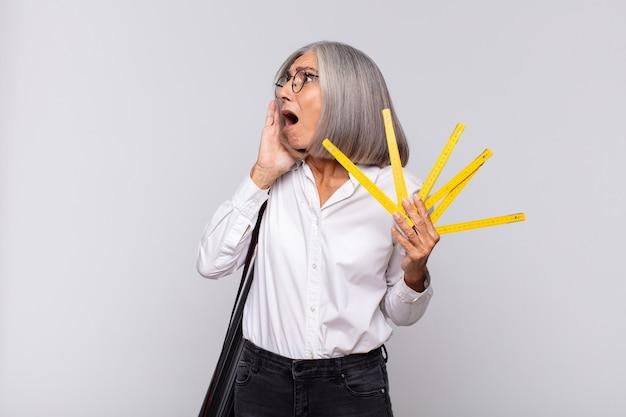 Donna di mezza età che si sente felice, eccitata e sorpresa, guardando di lato con entrambe le mani sul viso. concetto di architetto