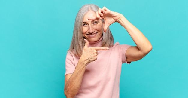 Donna di mezza età che si sente felice, amichevole e positiva, sorride e fa un ritratto o una cornice con le mani