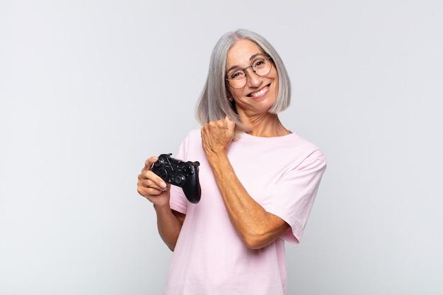 Donna di mezza età che si sente felice positiva e motivata di successo quando affronta una sfida o celebra buoni risultati giocando al concetto di console