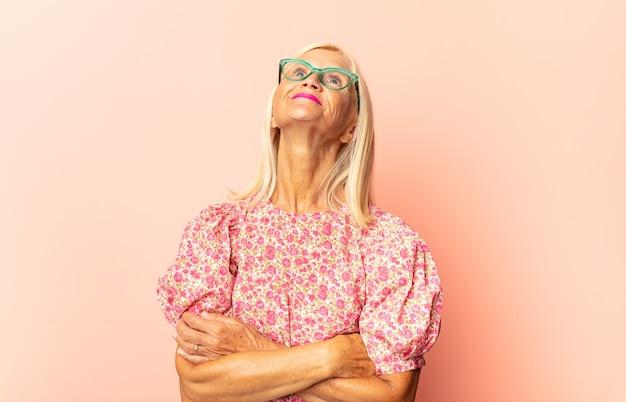 Donna di mezza età che si sente felice, orgogliosa e piena di speranza, chiedendosi o pensando, alzando lo sguardo per copiare lo spazio con le braccia incrociate