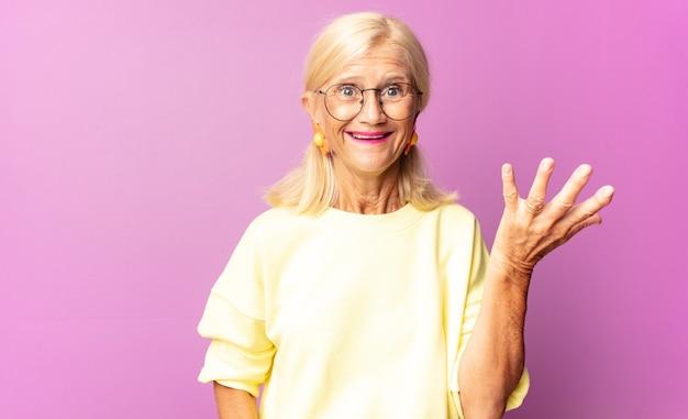 Donna di mezza età che si sente felice, sorpresa e allegra isolata