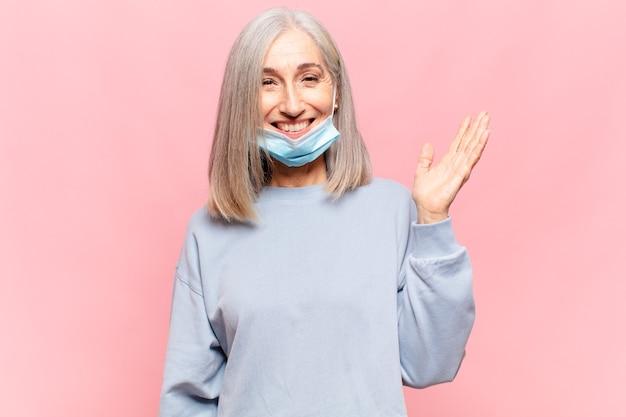 Donna di mezza età che si sente felice, sorpresa e allegra, sorridente con atteggiamento positivo, realizzando una soluzione o un'idea