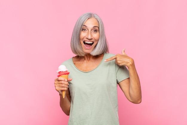 Donna di mezza età che si sente felice, sorpresa e orgogliosa, indicando se stessa con uno sguardo eccitato e stupito mentre mangia un gelato