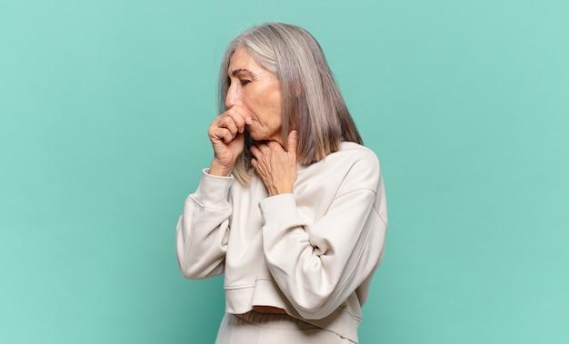 Donna di mezza età che si sente male con mal di gola e sintomi influenzali, tosse con la bocca coperta
