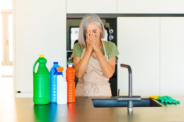 Donna di mezza età che si sente triste, frustrata, nervosa e depressa, coprendosi il viso con entrambe le mani, piangendo