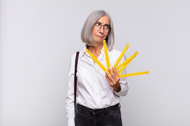 Donna di mezza età che si sente triste, turbata o arrabbiata e guarda di lato con un atteggiamento negativo, aggrottando le sopracciglia in disaccordo. concetto di architetto