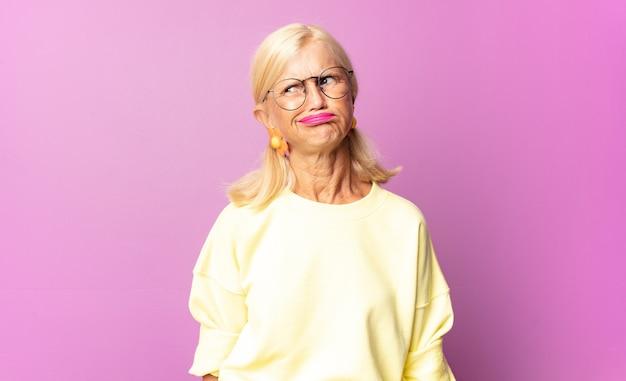 Donna di mezza età che si sente triste, arrabbiata o arrabbiata e guarda di lato con un atteggiamento negativo