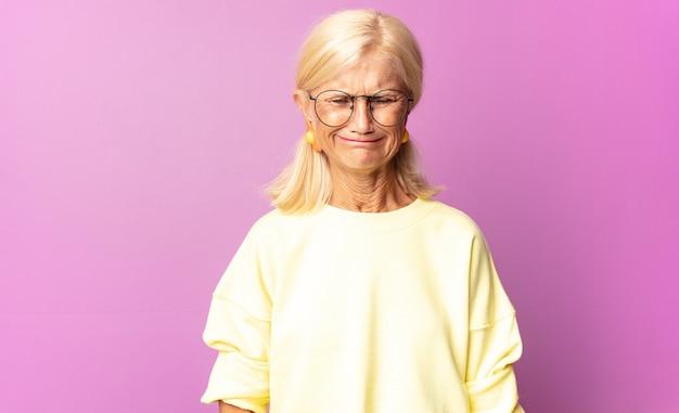 Donna di mezza età che si sente triste e piagnucolona con uno sguardo infelice, piange con un atteggiamento negativo e frustrato