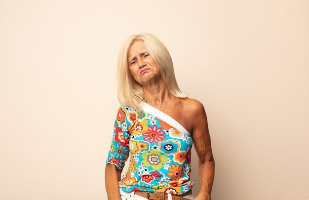 Donna di mezza età che si sente triste e piagnucolona con uno sguardo infelice