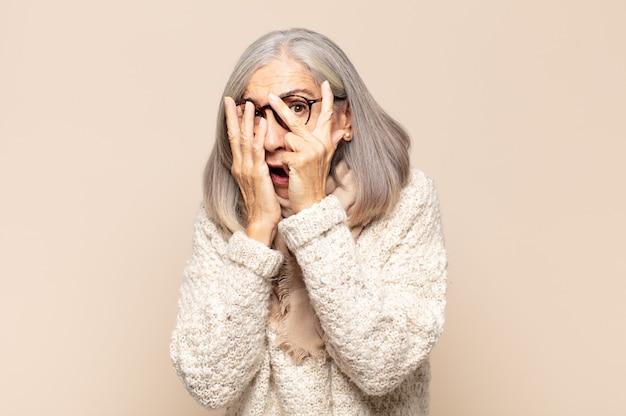Donna di mezza età che si sente spaventata o imbarazzata, sbirciando o spiando con gli occhi semicoperti dalle mani