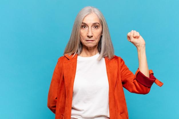 Donna di mezza età che si sente seria, forte e ribelle, alza il pugno, protesta o combatte per la rivoluzione