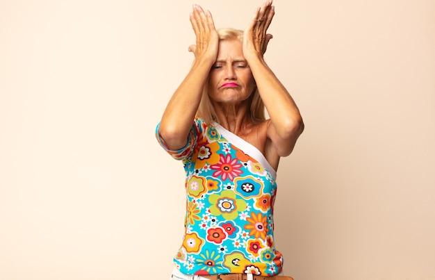Donna di mezza età che si sente stressata e ansiosa, depressa e frustrata con un mal di testa, alzando entrambe le mani alla testa