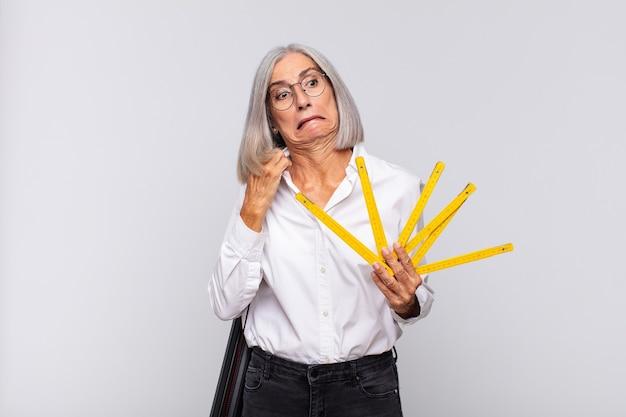 Donna di mezza età che si sente stressata, ansiosa, stanca e frustrata, tira il collo della camicia, sembra frustrata dal problema. concetto di architetto