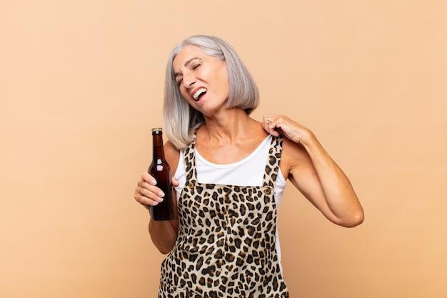 Donna di mezza età che si sente stressata, ansiosa, stanca e frustrata, tira il collo della camicia, sembra frustrata dal problema con una birra