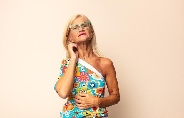 Donna di mezza età che si sente stressata, frustrata e stanca, strofinando il collo dolorante, con uno sguardo preoccupato e turbato