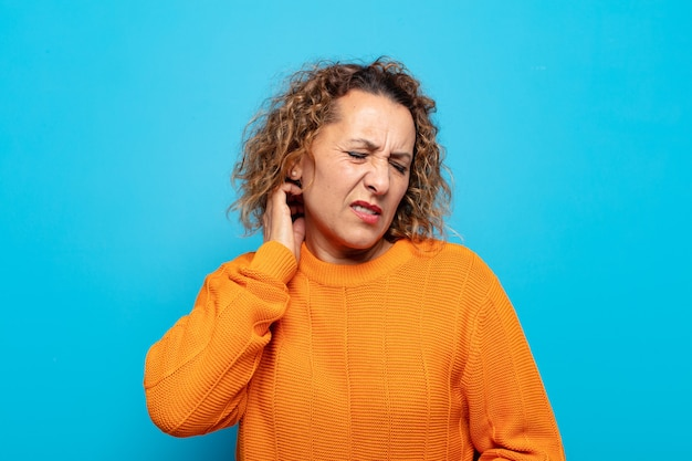 Donna di mezza età che si sente stressata, frustrata e stanca, strofinando il collo doloroso