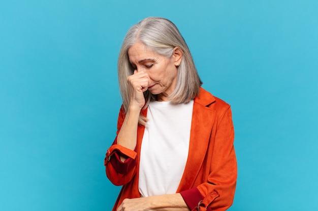 Donna di mezza età che si sente stressata, infelice e frustrata, si tocca la fronte e soffre di emicrania o forte mal di testa