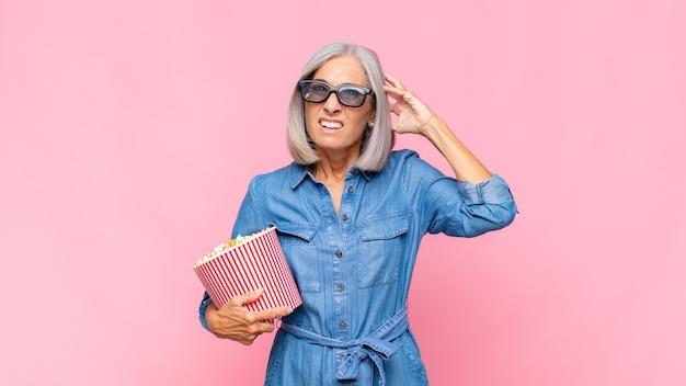 Donna di mezza età che si sente stressata, preoccupata, ansiosa o spaventata, con le mani sulla testa, in preda al panico al concetto di film di errore