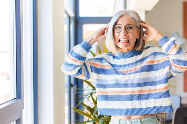 Donna di mezza età che si sente stressata, preoccupata, ansiosa o spaventata, con le mani sulla testa, in preda al panico per errore
