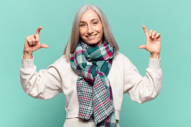 Donna di mezza età che incornicia o delinea il proprio sorriso con entrambe le mani, guardando positivo e felice, concetto di benessere