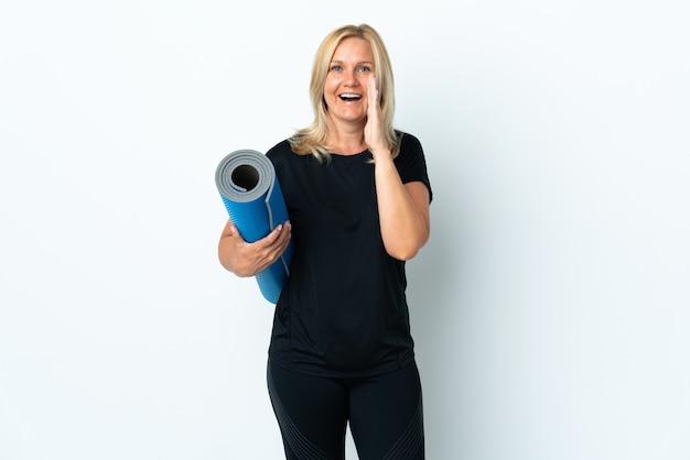 Donna di mezza età che va alle lezioni di yoga mentre si tiene un tappetino isolato su bianco che grida con la bocca spalancata