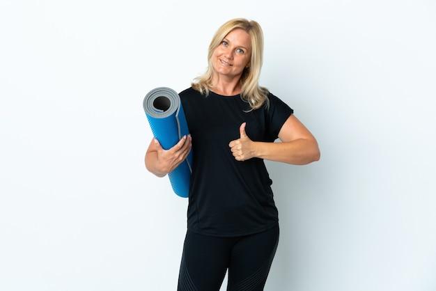 Donna di mezza età che va a lezioni di yoga tenendo un tappetino isolato su bianco con i pollici in su perché è successo qualcosa di buono