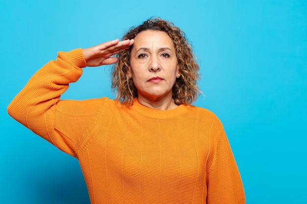Donna di mezza età che saluta con un saluto militare in un atto di onore e patriottismo, mostrando rispetto