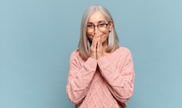 Donna di mezza età felice ed emozionata, sorpresa e stupita che copre la bocca con le mani, ridacchiando con un'espressione carina