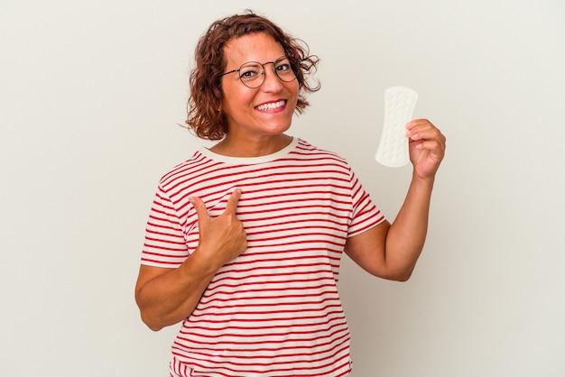 Donna di mezza età in possesso di un impacco isolato su sfondo bianco che punta con il dito su di te come se invitasse ad avvicinarsi.