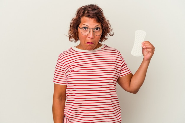 La donna di mezza età che tiene un impacco isolato su sfondo bianco alza le spalle e apre gli occhi confusi.