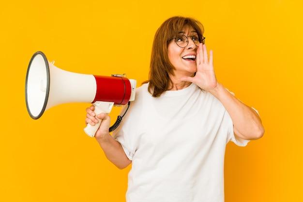 Donna di mezza età che tiene un megafono che grida e che tiene il palmo vicino alla bocca aperta