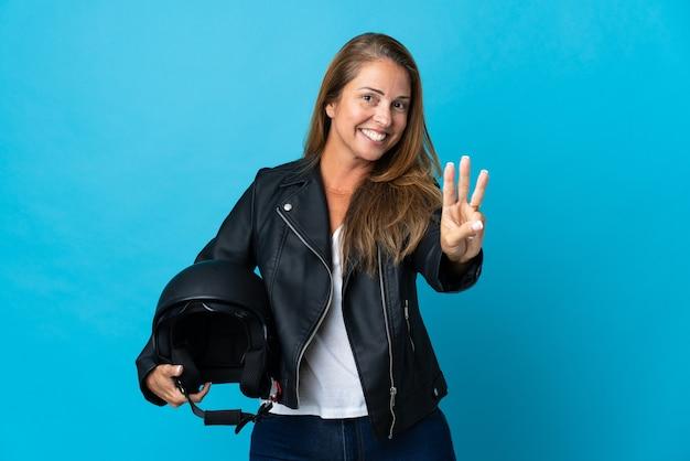 Donna di mezza età che tiene un casco da motociclista isolato sulla parete blu felice e contando tre con le dita