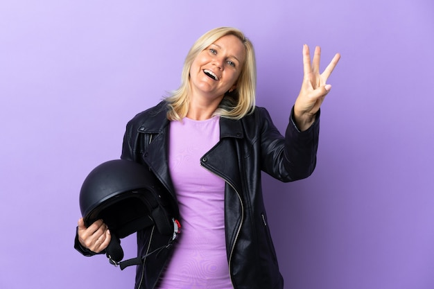 Donna di mezza età che tiene un casco da motociclista isolato sulla parete viola felice e contando tre con le dita