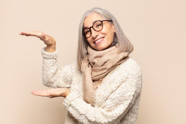 Donna di mezza età che tiene un oggetto con entrambe le mani sullo spazio della copia laterale, mostrando, offrendo o pubblicizzando un oggetto